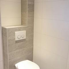 Badkamer met inloopdouche en hangend toilet.